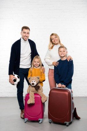 Photo pour Héhé, prêt à partir en vacances d'hiver avec des bagages en regardant la caméra sur fond blanc - image libre de droit