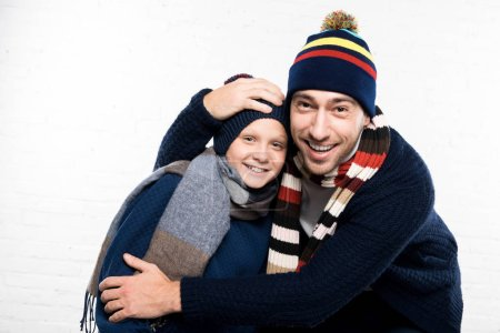 Photo for Smiling father and son in winter clothes on white background looking at camera - Royalty Free Image