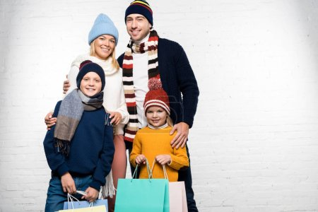 Photo for Happy family in winter clothes looking at camera and holding shopping bags - Royalty Free Image