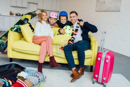 Photo pour Heureux famille assis sur le canapé avec des accessoires de ski et emballage pour les vacances d'hiver, concept de voyage - image libre de droit