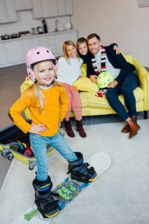 kid on snowboard posing on foreground while happy family having great time and packing for winter holidays