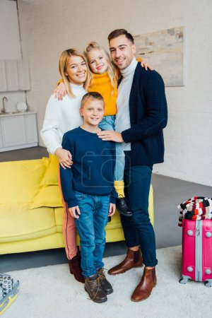 happy family ready for winter holidays and looking at camera with packed suitcase, travel concept
