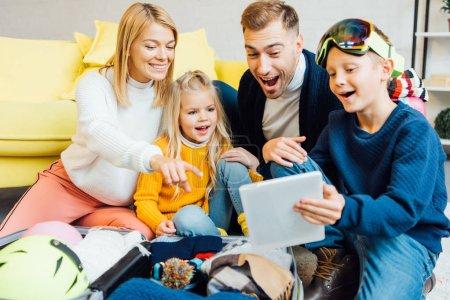 Photo pour Famille heureuse ayant beaucoup de temps, en utilisant la tablette numérique et l'emballage pour les vacances d'hiver - image libre de droit