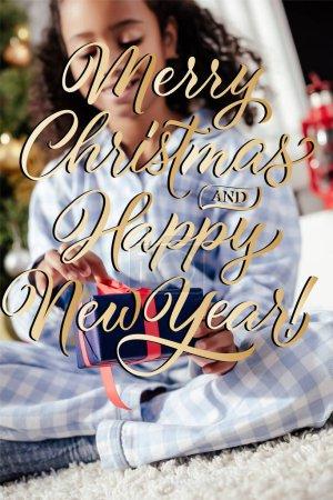 Photo pour Mise au point sélective de sourire adorable enfant afro-américain en pyjama ouverture de cadeau de Noël à la maison avec «merry christmas and happy new year» lettrage - image libre de droit