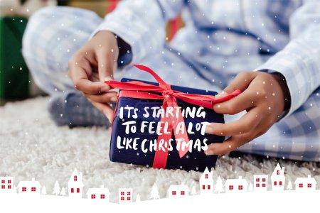 """Foto de Recortar imagen de niño afroamericano en pijamas apertura de Navidad en el piso con letras """"está empezando a sentir mucho como Navidad"""", de la nieve y casas ilustración - Imagen libre de derechos"""