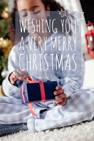 "selective focus of smiling adorable african american child in pajamas opening christmas gift at home with ""wishing you a very merry christmas"" lettering"
