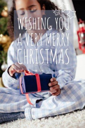 Photo pour Mise au point sélective de sourire adorable enfant afro-américain en pyjama ouverture de cadeau de Noël à la maison avec le lettrage «nous vous souhaitons un très joyeux Noël» - image libre de droit