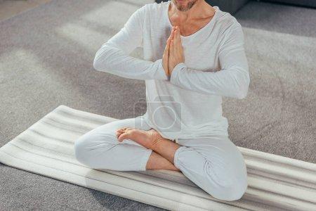 Photo pour Recadrée tir d'homme assis en position du lotus et de méditer avec namaste le geste sur le tapis d'yoga - image libre de droit
