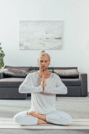 adult man with closed eyes meditating in lotus position and namaste gesture at home