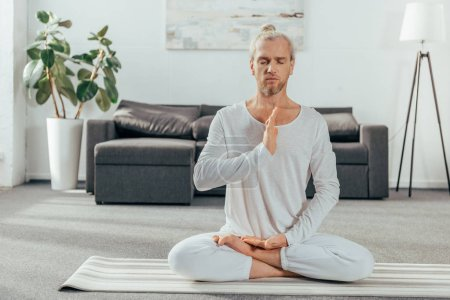 adult man with closed eyes meditating in lotus position on yoga mat at home