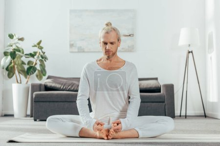 man meditating in lotus position on yoga mat at home