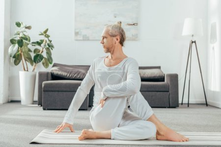 concentrated adult man sitting in yoga pose on mat and looking away at home