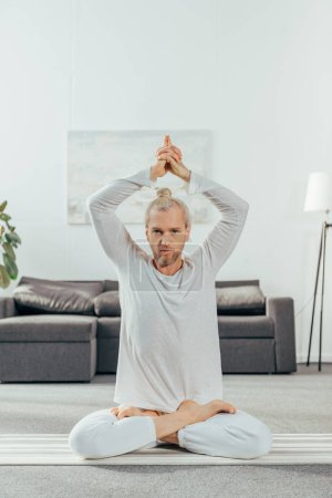 man meditating in lotus position with mudra sign and looking at camera