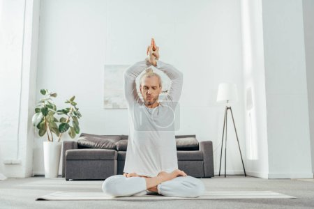 adult man meditating in lotus position with mudra sign on yoga mat at home