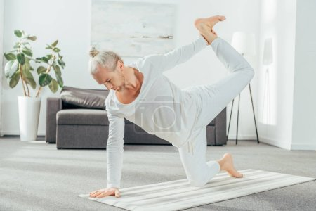 full length view of barefoot adult man practicing yoga at home