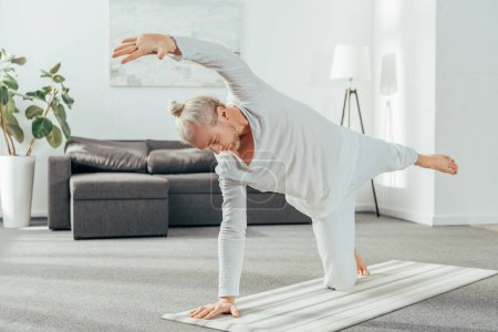 sporty adult man standing in asana on yoga mat at home