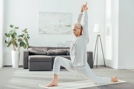 side view of man practicing Crescent Lunge on the Knee yoga pose at home