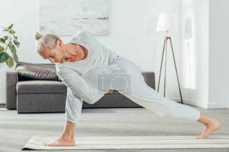 Photo for Man standing in Bound Side Angle pose on yoga mat at home - Royalty Free Image