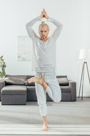 full length view of man standing in tree pose on yoga mat at home