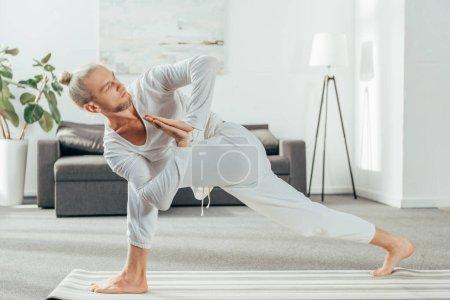 man standing in Revolved Side Angle exercise, Parivrtta Parsvakonasana pose on yoga mat at home