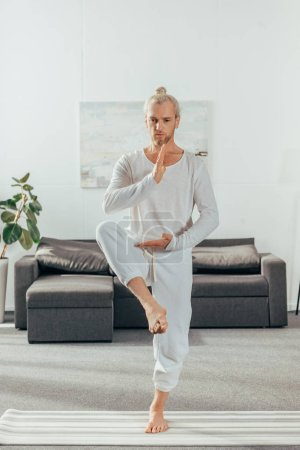 sporty adult man balancing in yoga pose on mat at home