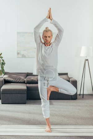sporty adult man practicing tree pose on yoga mat at home
