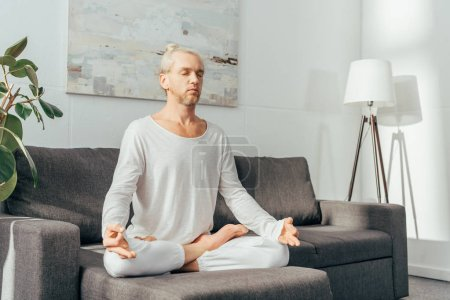 adult man with closed eyes meditating in lotus position on sofa at home