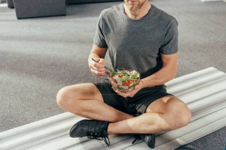 Photo for Cropped shot of athletic man in sportswear sitting on yoga mat and holding bowl with vegetable salad at home - Royalty Free Image