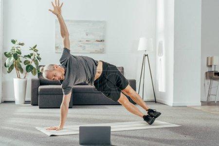 Photo pour Sport homme Sportswear pratiquer planche de côté et en regardant de portable - image libre de droit