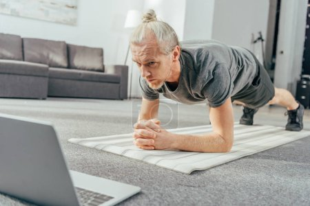 sporty adult man doing plank exercise and looking at laptop