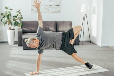 Photo pour Vue grand angle d'athlétisme homme Sportswear pratiquer planche de côté sur le tapis d'yoga à la maison - image libre de droit