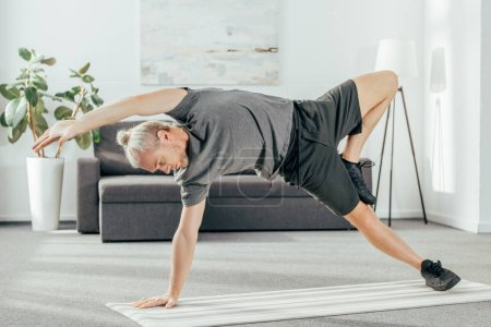 flexible athletic man in sportswear practicing side plank on yoga mat at home