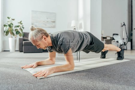 sporty adult man in sportswear doing plank exercise on yoga mat at home