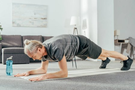 athletic man in sportswear doing plank exercise on yoga mat at home