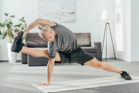 sporty adult man balancing and stretching on yoga mat at home