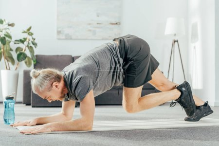 Photo for Side view of athletic man in sportswear training on yoga mat at home - Royalty Free Image