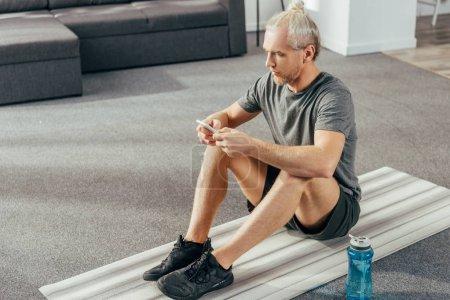 Photo pour Vue d'angle élevé d'adulte homme Sportswear siégeant à tapis d'yoga et en utilisant le smartphone à la maison - image libre de droit