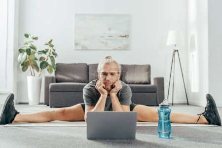 sporty adult man doing split on yoga mat and looking at laptop