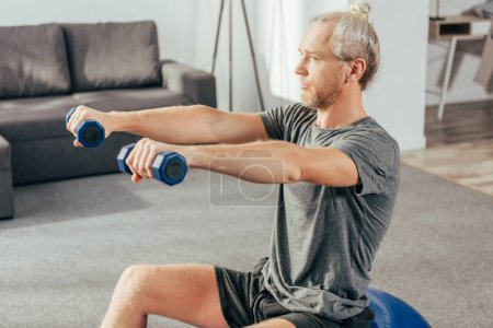 Photo for Sporty adult man sitting on fit ball and training with dumbbells at home - Royalty Free Image