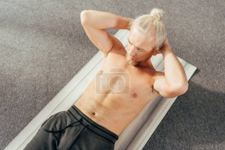 high angle view of shirtless man doing abs exercise on yoga mat at home