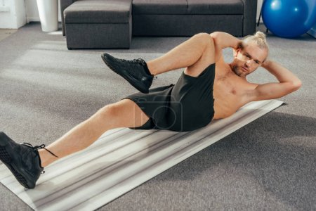 muscular shirtless man doing abs exercise on yoga mat at home
