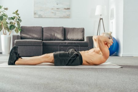 side view of shirtless man doing abs exercise on yoga mat at home
