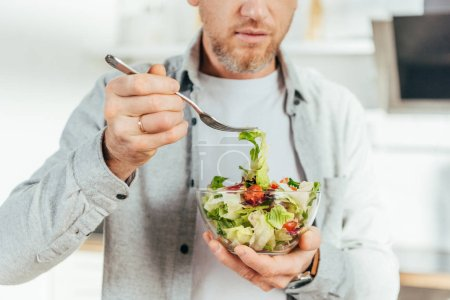 Photo for Cropped shot of man eating vegetable salad at home - Royalty Free Image