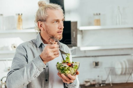 Photo for Handsome man eating vegetable salad and looking away in kitchen - Royalty Free Image