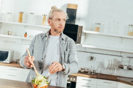 adult man cooking vegetable salad and looking away in kitchen