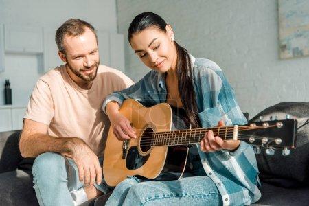 Photo pour Beau mari enseignant belle femme à jouer de la guitare acoustique - image libre de droit
