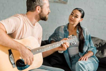 Photo for Handsome husband playing acoustic guitar while beautiful wife listening him - Royalty Free Image
