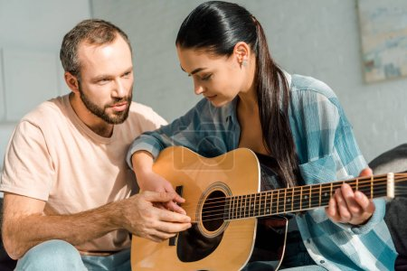 Photo for Handsome husband teaching beautiful wife to play acoustic guitar - Royalty Free Image