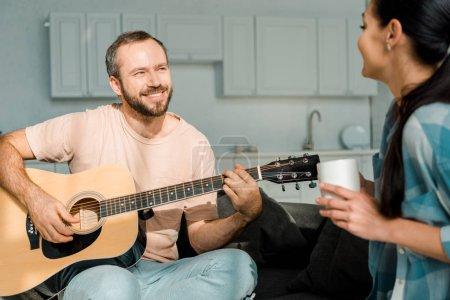 Photo pour Souriant mari jouer acoustique de la guitare tandis que femme écoute - image libre de droit