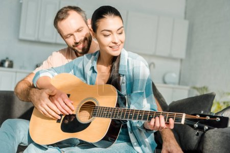Photo for Happy husband teaching smiling wife to play acoustic guitar - Royalty Free Image